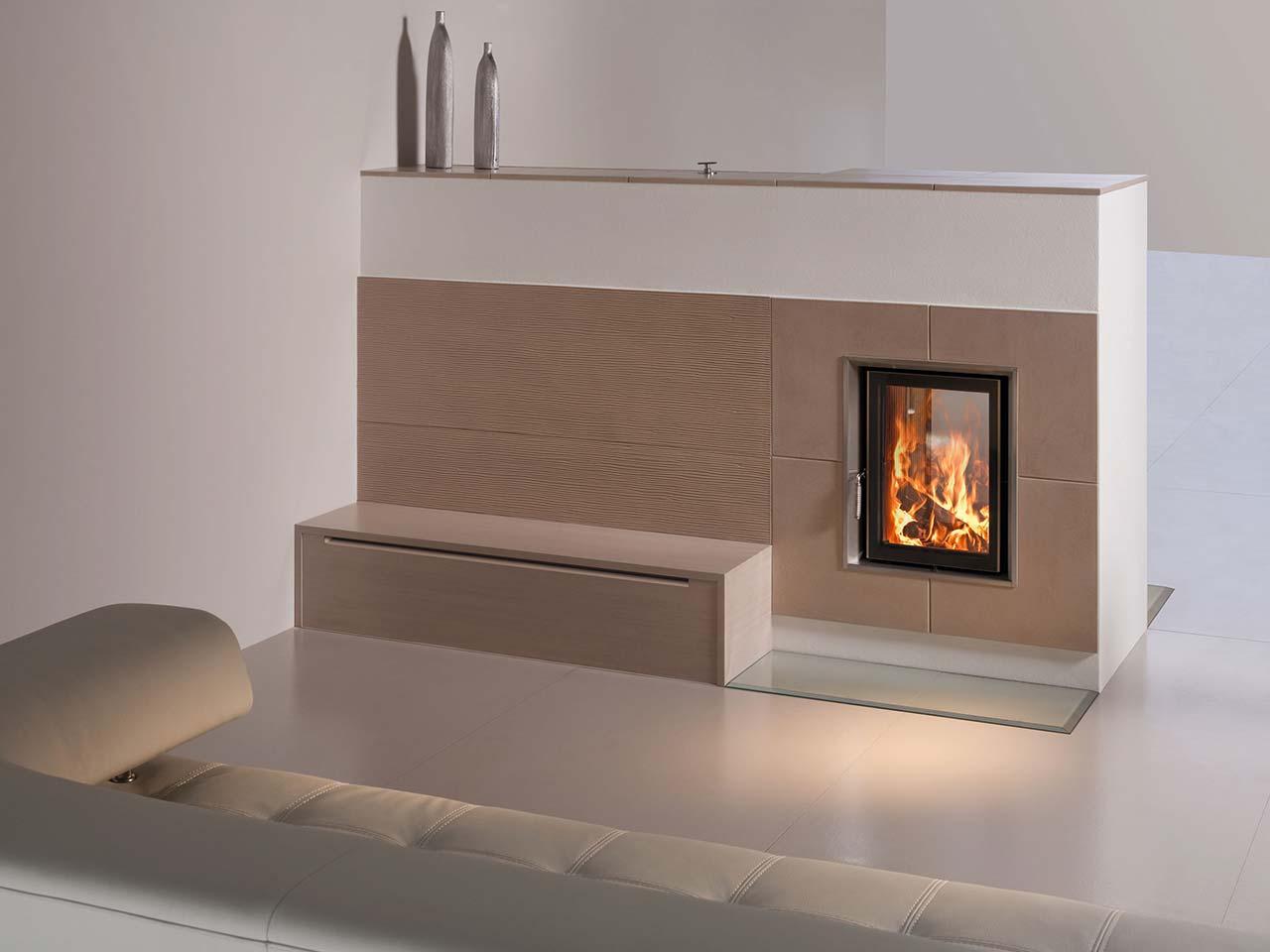 Eleganter Kachelofen mit Sitzbank und Feuerfenster als Raumteiler. Foto: Sommerhuber