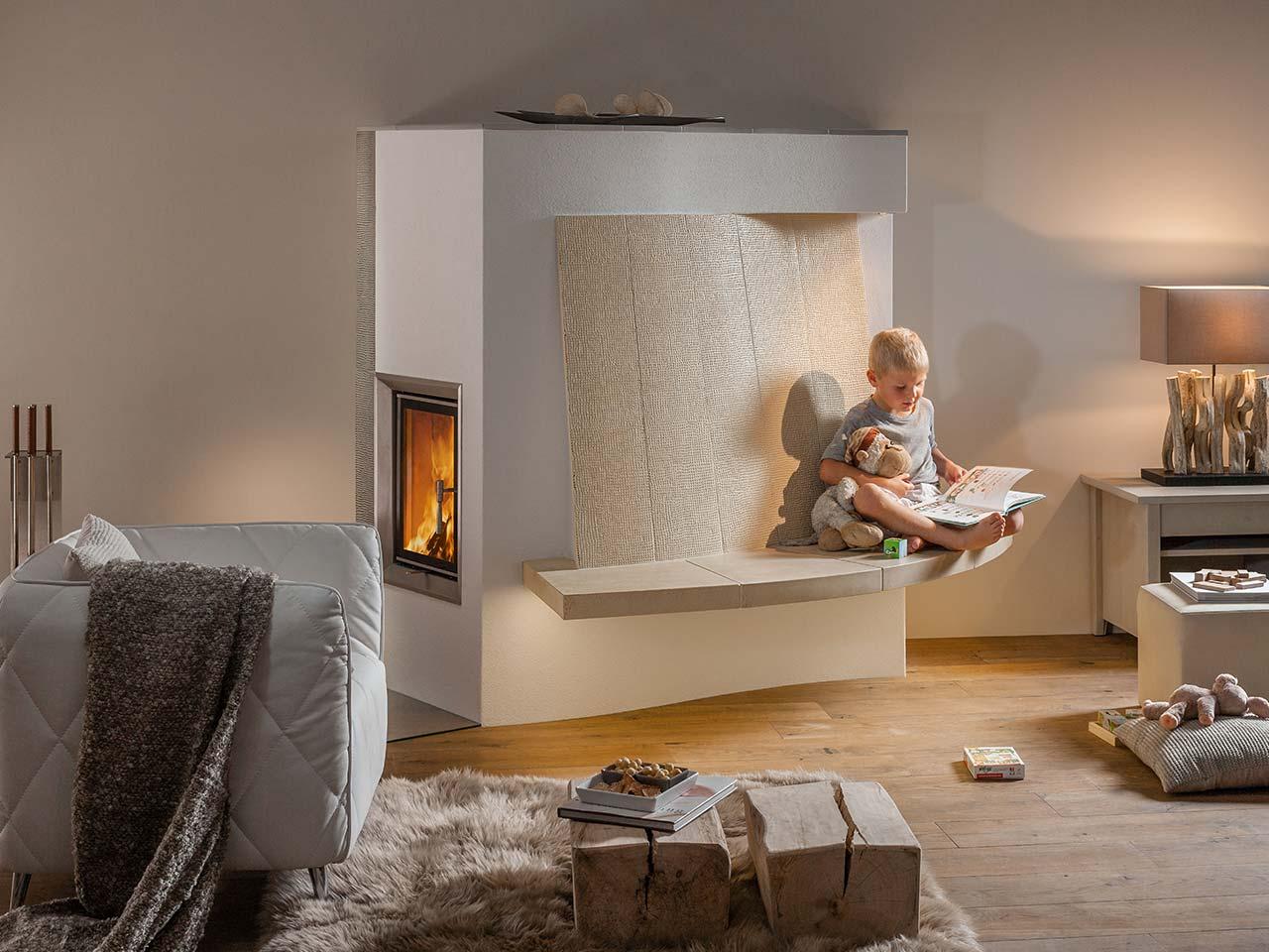 Moderner, eleganter Landhaus-Kachelofen mit seitlicher Feuertür und Sitzfläche aus Naturstein. Foto: Sommerhuber