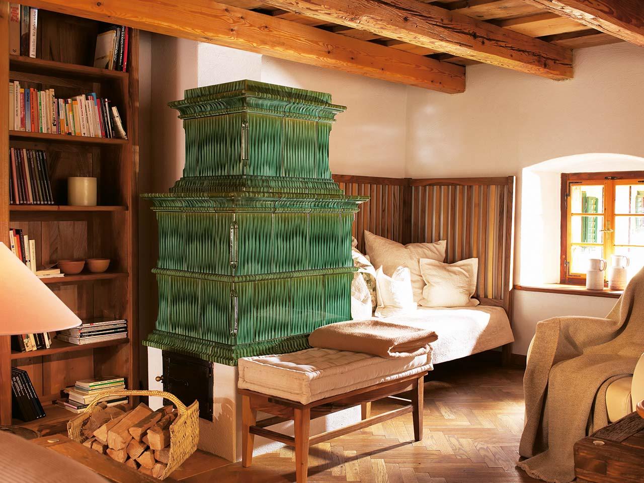 Klassischer Kachelofen mit gepolsterter Landhaus Sitzbank und grünen Kacheln. Foto: Sommerhuber